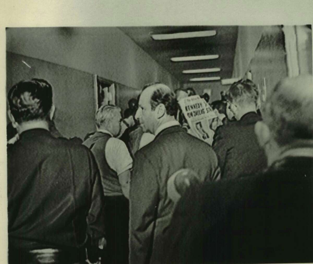 """Jack Ruby, profiled man in foreground, is seen in crowded corridor at Dallas police headquarters on the night of November 22, 1963, the date on which President Kennedy was assassinated. Two days later, Sunday, November 24, Ruby again was in Dallas police headquarters at which time he shot and killed Lee Harvey Oswald, Kennedy's accused assassin. This picture was taken from unused movie film during preparation of the CBS program """"November 22 and the Warren Report"""""""