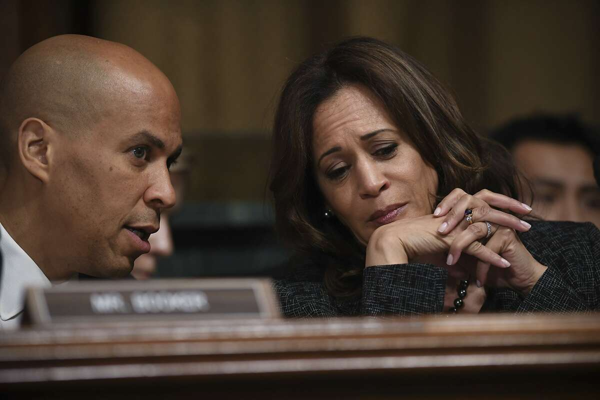 US Senators Cory Booker (L) and Kamala Harris (R) chat as Christine Blasey Ford, the woman accusing Supreme Court nominee Brett Kavanaugh of sexually assaulting her at a party 36 years ago, testifies before the US Senate Judiciary Committee on Capitol Hill in Washington, DC, September 27, 2018.(Saul Loeb/Pool Photo via AP)
