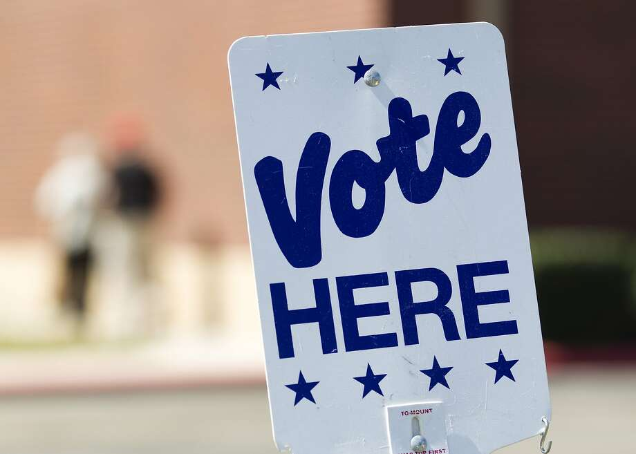 A sign reading 'Vote Here' is seen at a polling location. Photo: Jason Fochtman, Houston Chronicle