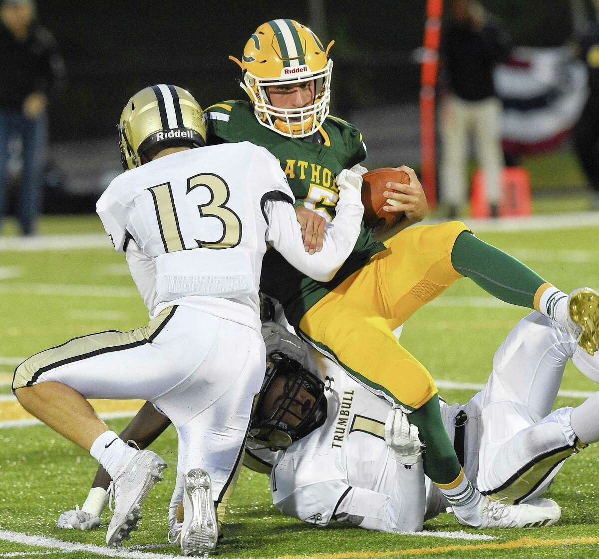 Trinty Catholic quarterback Sam Pensiero (5) is sacked by Trumbull's Nolan Shay (13) and Raymond Leonzi (1) during the second quarter Friday in Stamford.