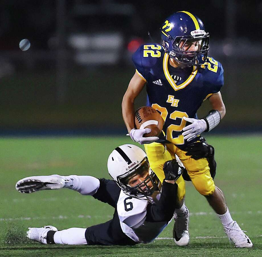 East Haven's Jacob Araujo attempts to escape a tackle by Xavier's Mike Astorino on Friday. Photo: Catherine Avalone / Hearst Connecticut Media / New Haven Register