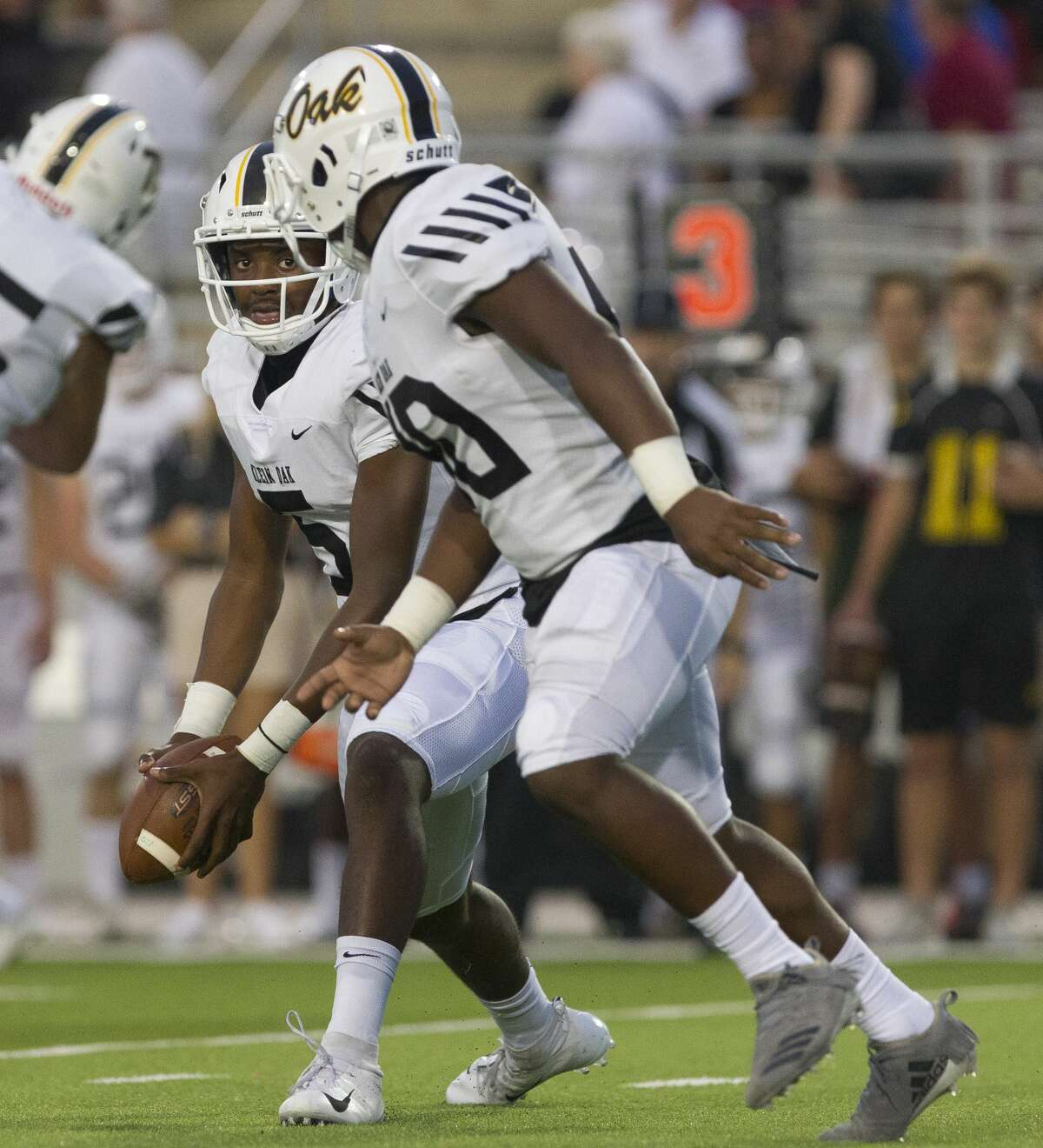 Klein Oak quarterback Montrell Bolton (5) pitches the ball to running back Charles Garrett (40) during the first quarter of a District 15-6A high school football game at Woodforest Bank Stadium, Friday, Sept. 28, 2018, in Shenandoah.
