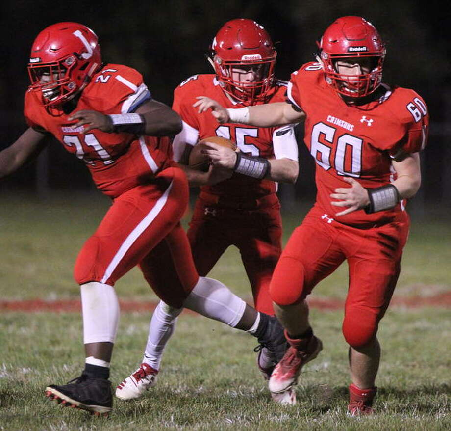Jacksonville's Chris Pulley (left) and Wil Tomhave provide a wall for quarterback Ryan Maul to run behind during a game against Lanphier Friday night in Jacksonville. Photo: Dennis Mathes | Journal-Courier
