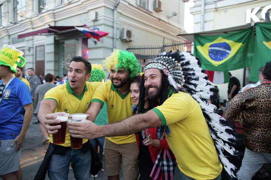 Supporters of the Brazil soccer team toast with pints of beer as they pose for a photograph in Moscow on June 15, 2018. Photo: Bloomberg Photo By Andrey Rudakov. / © 2018 Bloomberg Finance LP
