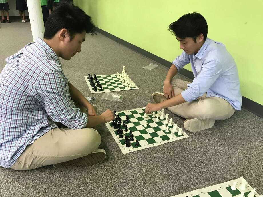 Brothers Jake and George Wang, co-founders of Chess Haven, demonstrate a chess match at Elm City Montessori School. Photo: Brian Zahn/Hearst Connecticut Media