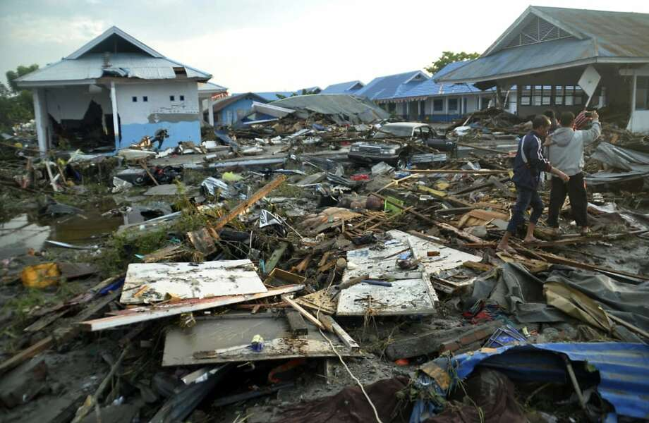 Indonesian men survey the damage following earthquakes and a tsunami in Palu, Central Sulawesi, Indonesia, Saturday, Sept. 29, 2018. A tsunami swept away buildings and killed large number of people on the Indonesian island of Sulawesi, dumping victims caught in its relentless path across a devastated landscape that rescuers were struggling to reach Saturday, hindered by damaged roads and broken communications. (AP Photo/Rifki) Photo: Rifki / Associated Press