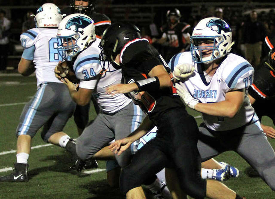 Jersey fullback Brian McDonald (34) runs through a hole off the block of Zac Mueller in Mississippi Valley Conference football action Friday night in Waterloo. McDonald rushed for 116 yards and two TDs in the Panthers' 28-26 victory. Photo: Greg Shashack | The Telegraph
