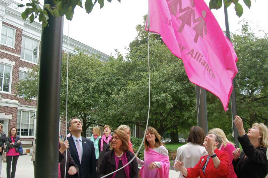 Breast Cancer Alliance and its supporters, including First Selectman Peter Tesei, raise the pink flag in front of Town Hall in a previous year. Greenwich will mark Breast Cancer Awareness Month throughout October. Photo: File / Ken Borsuk / Hearst Connecticut Media / Greenwich Time