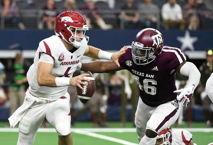 Arkansas quarterback Ty Storey (4) tries to avoid the pressure from Texas A&M defensive lineman Landis Durham (46) during the first quarter of an NCAA college football game, Saturday, Sept. 29, 2018, in Arlington, Texas. Storey was sacked on the play. (AP Photo/Jeffrey McWhorter)