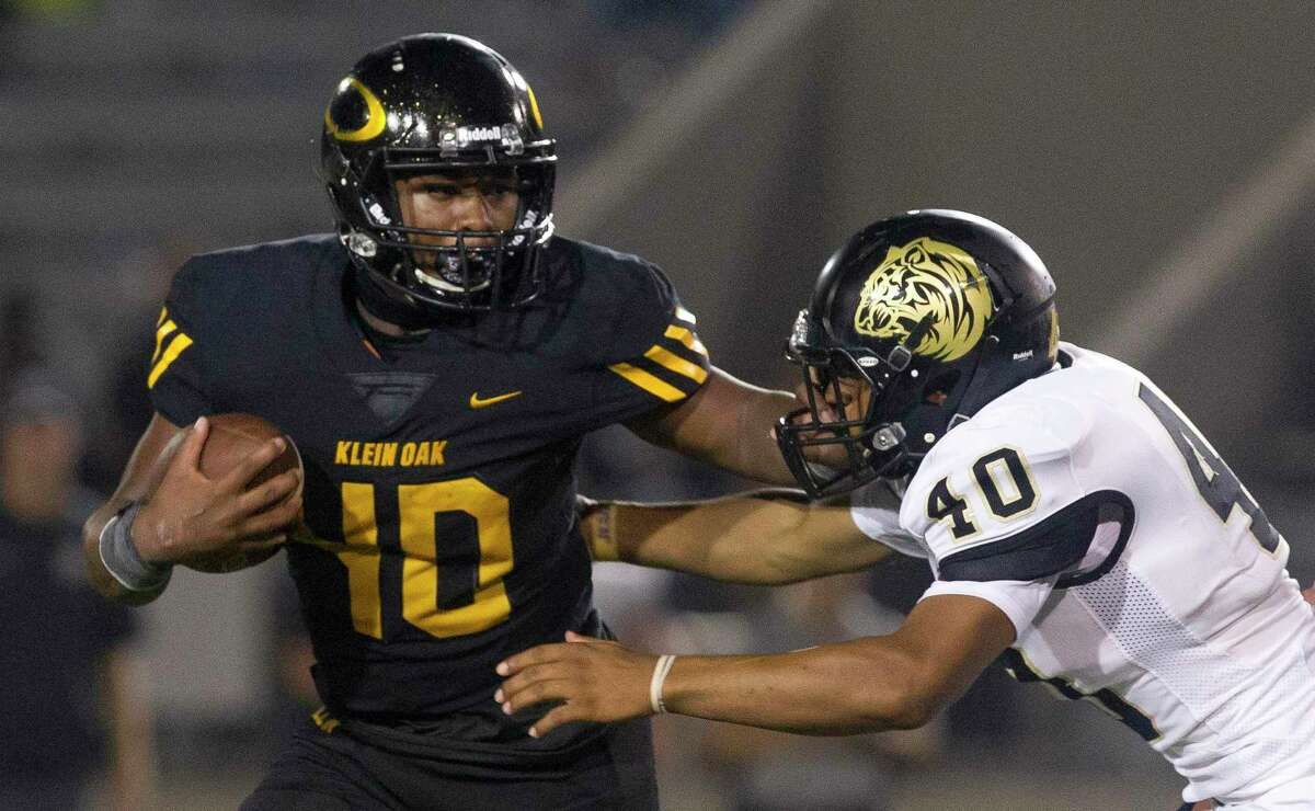 Klein Oak running back Charles Garrett (40) stiff-arms Conroe linebacker Cartravion Houston (40) during the fourth quarter of a District 15-6A game at Klein Memorial Stadium on Saturday, Sept. 22, 2018, in Spring.