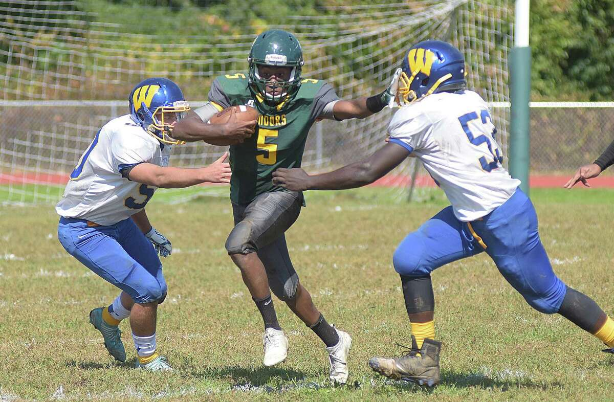 O?'Brien Tech?'s Jonte Roc (5) splits a pair of Wilcox Tech defenders to pick up yardage during Saturday?'s high school football game against Wilcox Tech in Ansonia.