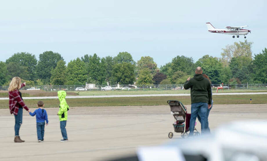 Families watch a small plane make its landing Saturday during the 24th annual Wings and Wheels Fly In at St. Louis Regional Airport in Bethalto. Photo: Nathan Woodside | The Telegraph