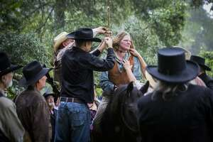 """Debra Elledge, center, participates in a reenactment of a woman being hanged because she was charged for illegally voting while dressed as a man, for cutting off """"part"""" of her husband and for preaching. The reenactment took place during the annual Heritage Days event hosted by the San Jacinto County Historical Commission, Saturday, Sept. 29, 2018, in Coldspring."""