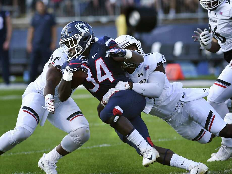 UConn running back Kevin Mensah (34) is stopped during the first half against Cincinnati on Saturday. Photo: Stephen Dunn / Associated Press / Copyright 2018 The Associated Press. All rights reserved