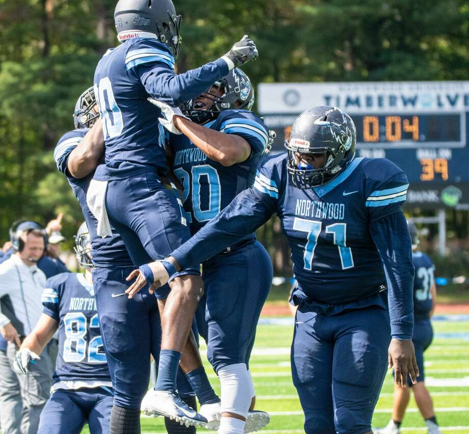 Timberwolves Roq Williams celebrates with teammates after catching a bounding ball in the end zone for a touchdown against Grand Valley Saturday. Steven Simpkins   for the Daily News Photo: Steven Simpkins/Midland Daily Ne, Steven Simpkins