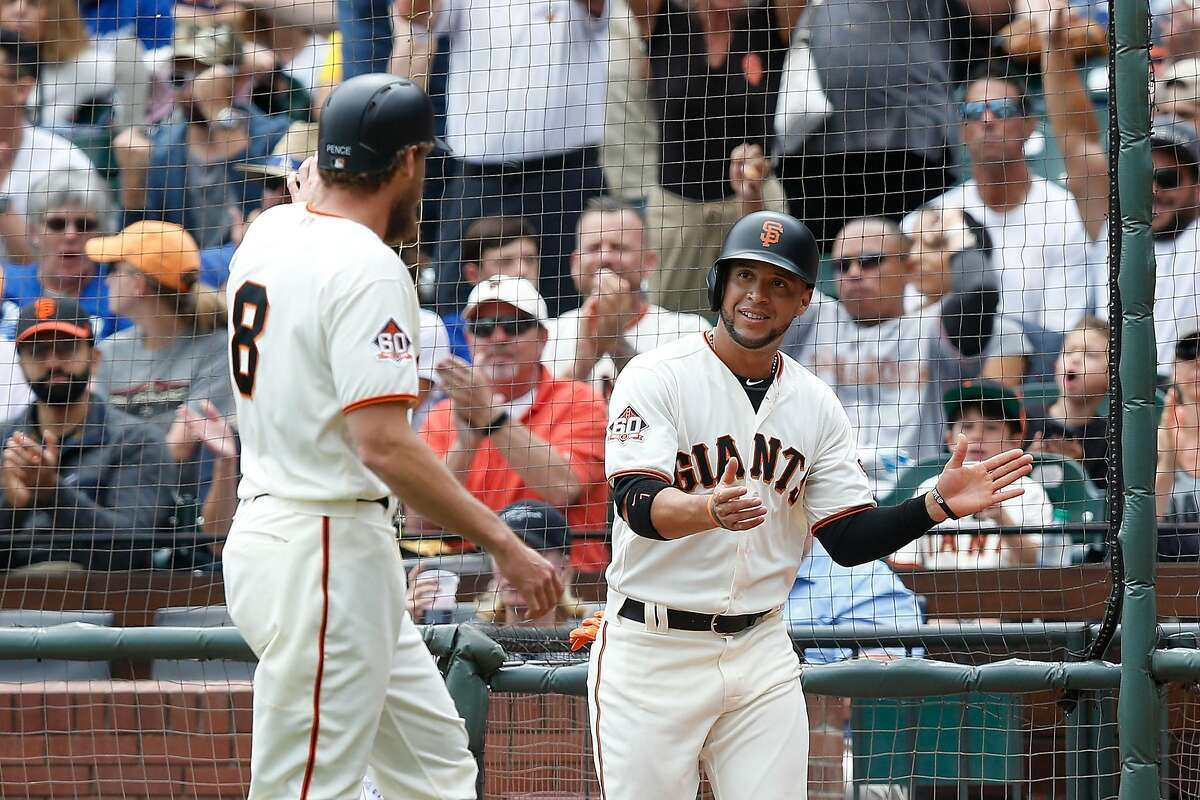 Hunter Pence #8 and Gregor Blanco #1 of the San Francisco Giants celebrate after scoring on a two-run single by teammate Joe Panik #12 in the bottom of the third inning against the Los Angeles Dodgers at AT&T Park on September 29, 2018 in San Francisco, California.