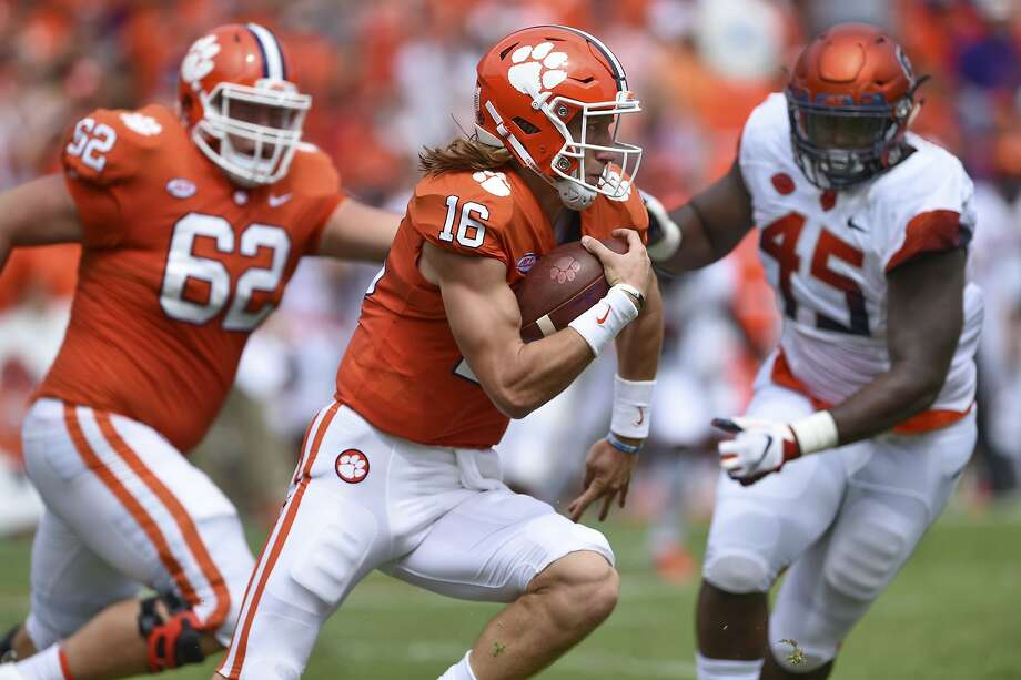 Clemson quarterback Trevor Lawrence scrambles out of the pocket with blocking help from Cade Stewart. Photo: Richard Shiro / Associated Press