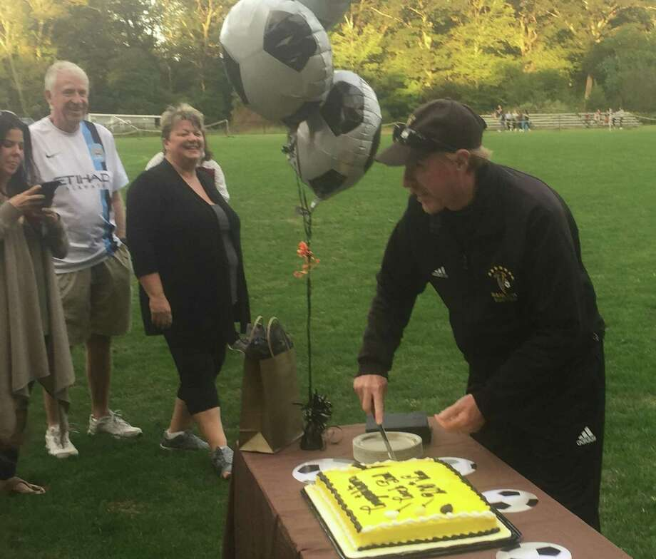 Joel Barlow High School boys soccer coach Paul Winstanley makes the first slice into a cake celebrating his 200th career victory following the Falcons' 3-1 victory over Naugatuck at Joel Barlow High School in Renning, Sept. 29, 2018. Photo: Richard Gregory