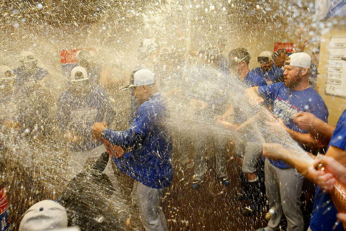 Manager Dave Roberts #30 of the Los Angeles Dodgers is sprayed with champagne as Dodgers players celebrate after clinching a post season spot by defeating the San Francisco Giants at AT&T Park on September 29, 2018 in San Francisco, California.