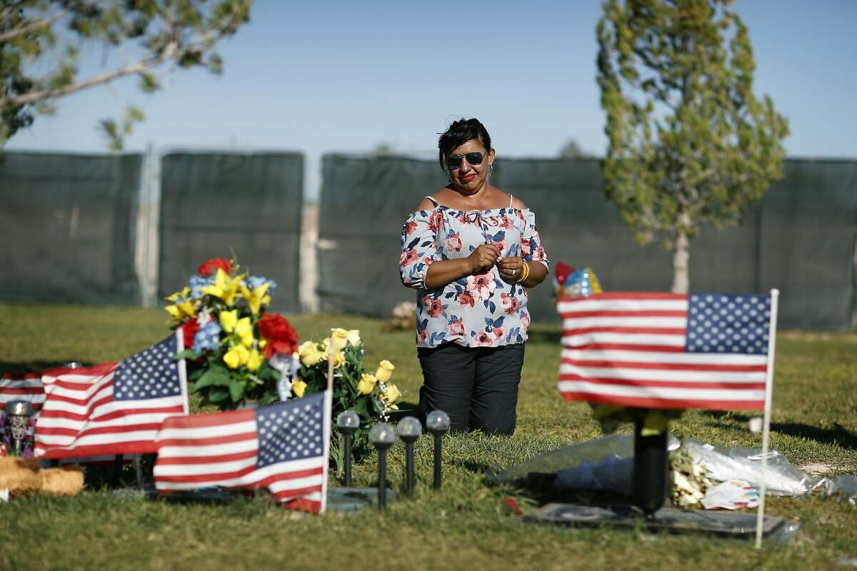 Angelica Cervantes kneels at her son Erick Silva's grave Saturday, Sept. 29, 2018, in Las Vegas. Silva was one of 58 people killed Oct. 1, 2017, in the deadliest mass shooting in modern U.S. history. Silva was working as a security guard at the Route 91 Harvest Festival and was shot while helping people climb over a barricade to escape the gunfire. (AP Photo/John Locher)