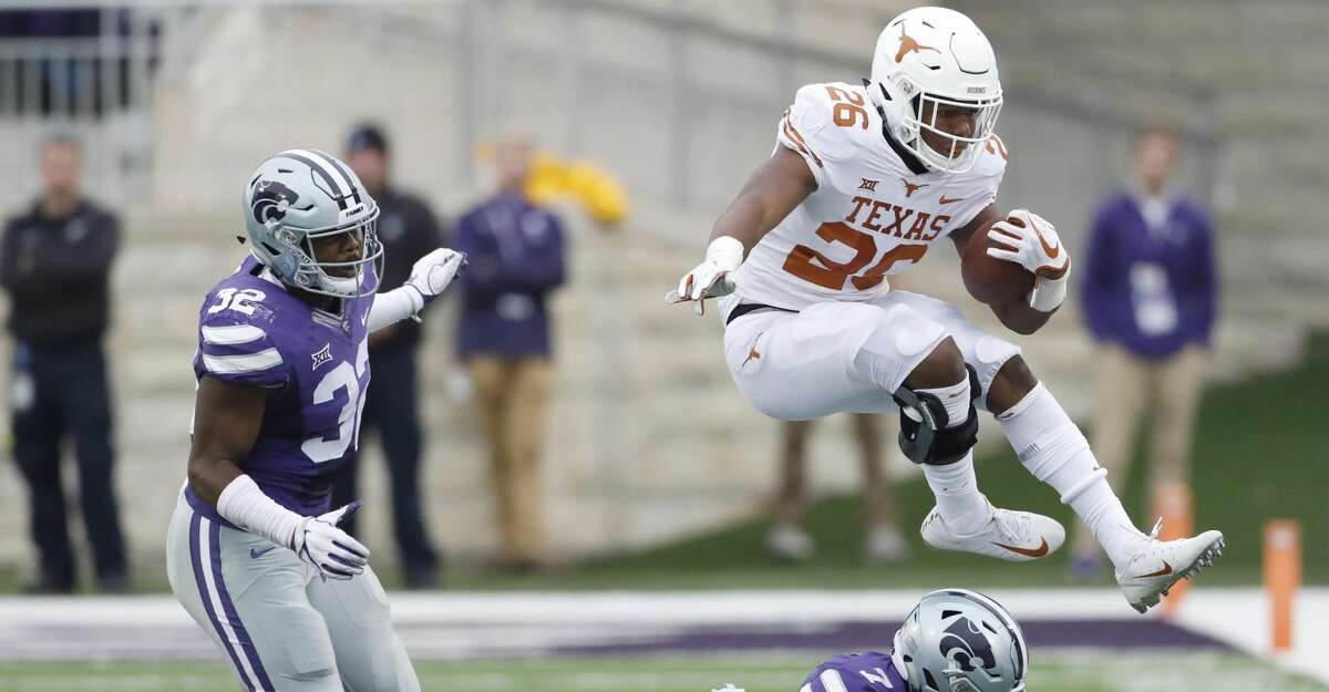 Texas running back Keaontay Ingram (26) jumps over Kansas State safety Eli Walker (7) as he rushes for a first down as Kansas State linebacker Justin Hughes (32) also defends during the fourth quarter of a college football game in Manhattan, Kan., Saturday, Sept. 29, 2018. (AP Photo/Colin E. Braley)