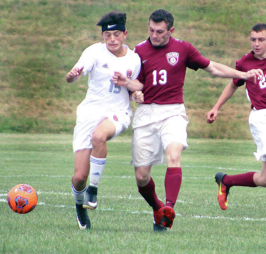 Roxana's Colton Crawford (15) and EA-WR's Jared Liley (13) battle for the ball Saturday in prep soccer action at the Wood River Soccer Park. Photo: Pete Hayes | The Telegraph