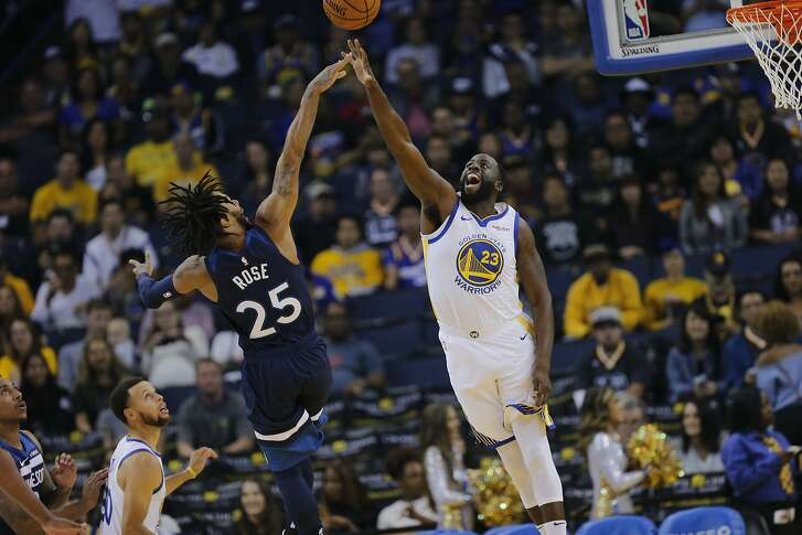 Golden State Warriors forward Draymond Green (23) defends Minnesota Timberwolves guard Derrick Rose (25) during the first half of an NBA preseason game between the Golden State Warriors and Minnesota Timberwolves at Oracle Arena on Saturday, Sept. 29, 2018, in Oakland, Calif.