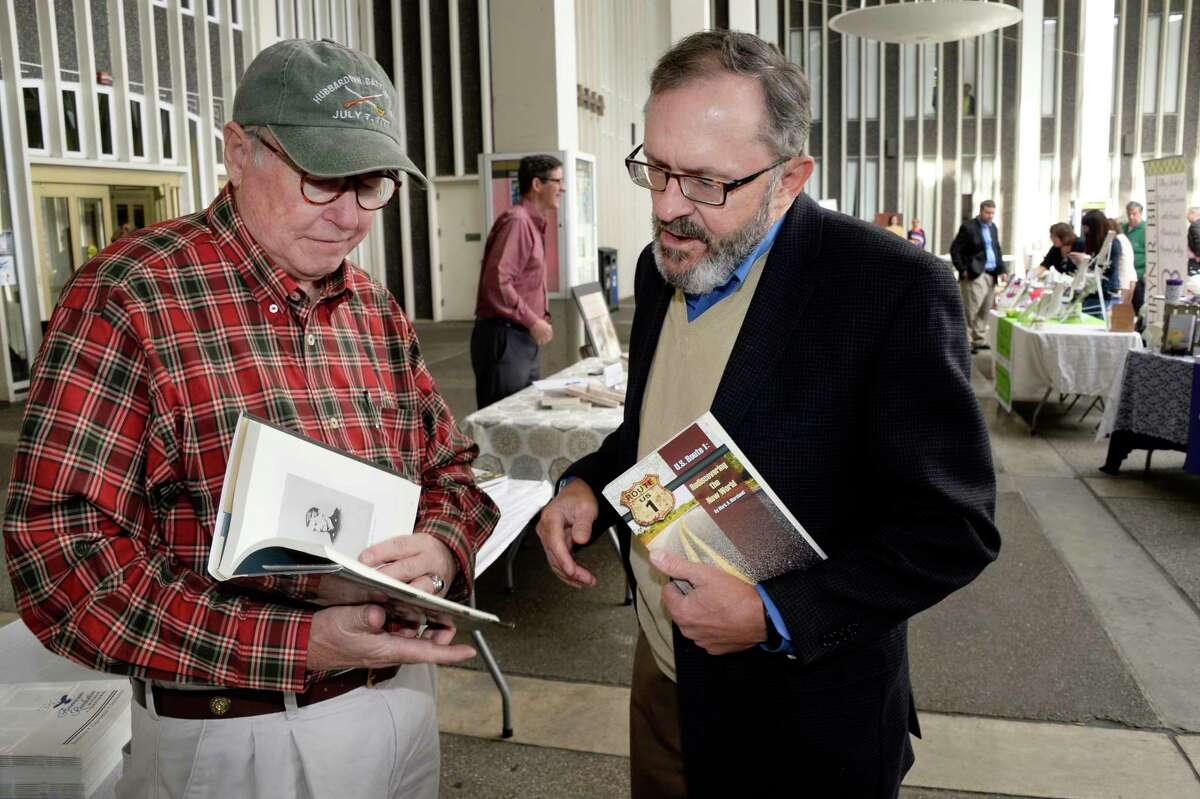 Authors Bruce Venter, left, of Goochland, Virginia and Mark Marchand of Clifton Park compare notes during the Albany Book Festival at UAlbany Saturday Sept. 29, 2018 in Albany, NY. (John Carl D'Annibale/Times Union)