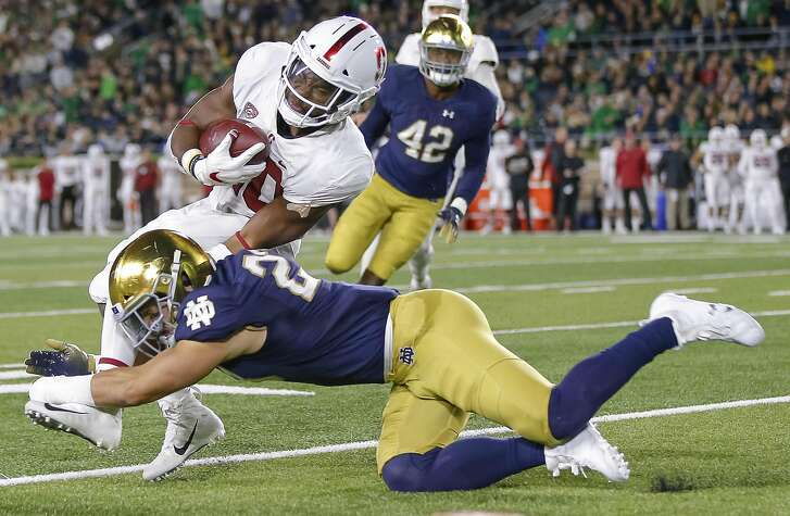 SOUTH BEND, IN - SEPTEMBER 29: Bryce Love #20 of the Stanford Cardina runs the ball and is tackled by Drue Tranquill #23 of the Notre Dame Fighting Irish during the first half of the game at Notre Dame Stadium on September 29, 2018 in South Bend, Indiana. (Photo by Michael Hickey/Getty Images)