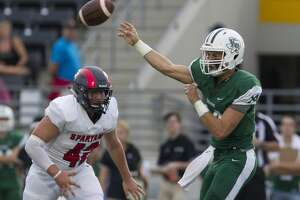 Kingwood Park quarterback Sam Johansen (14) throws under pressure by Porter defensive lineman Logan Martin (42) during the second quarter of a District 9-5A high school football game at Turner Stadium, Saturday, Sept. 29, 2018, in Humble.