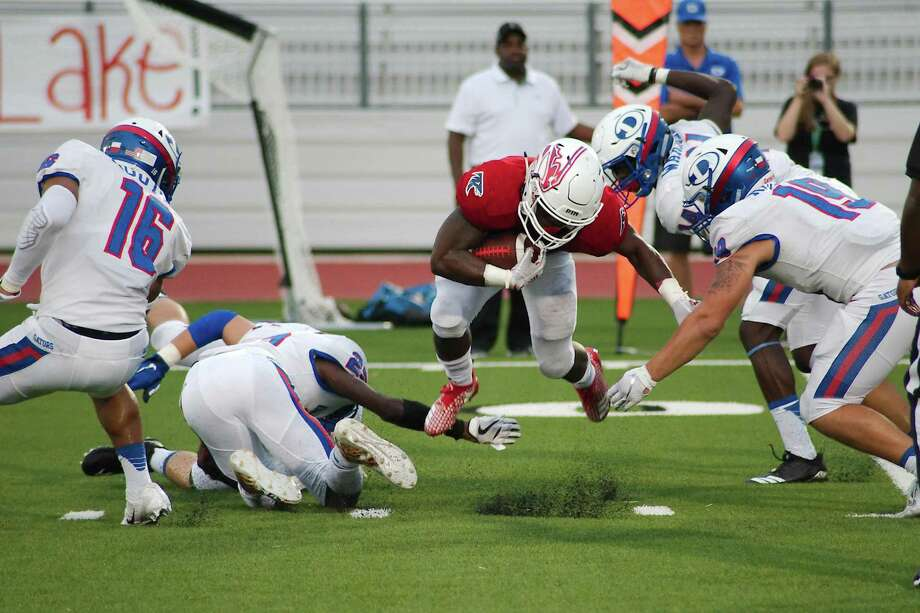 f3a5d1667e Clear Lake s Brendon Holmes (1) is tripped up by Dickinson defenders  Saturday at Challenger