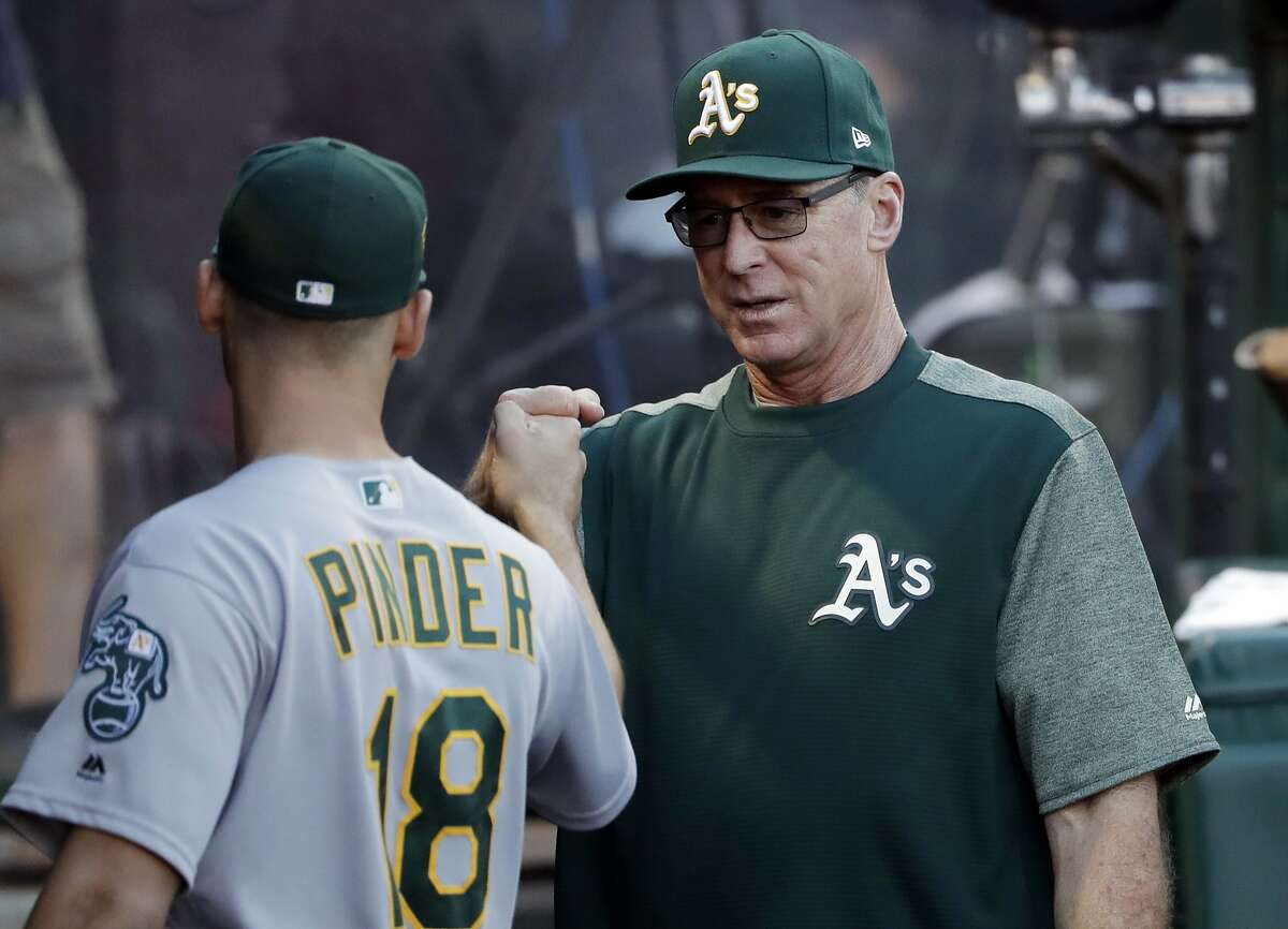 Oakland Athletics manager Bob Melvin, right, gives a fist-bump to Chad Pinder before the team's baseball game against the Los Angeles Angels on Saturday, Sept. 29, 2018, in Anaheim, Calif. (AP Photo/Marcio Jose Sanchez)