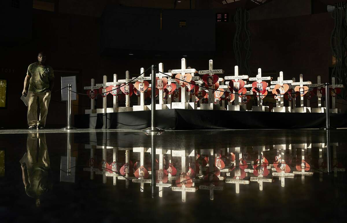 In this Friday, Sept. 21, 2018, photo, a man walks by crosses on display at the Clark County Government Center in Las Vegas. The crosses had been part of a makeshift memorial along the Las Vegas Strip erected in memory of the victims of the Oct. 1, 2017 mass shooting at a country music festival in Las Vegas. A committee chaired by Nevada Gov. Brian Sandoval will work to design, fund and build a permanent memorial. (AP Photo/John Locher)