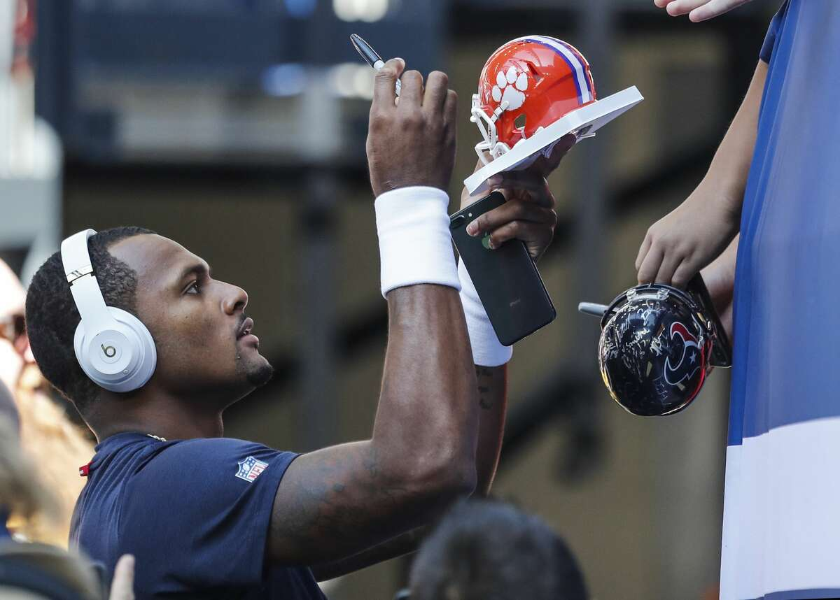 Houston Texans quarterback Deshaun Watson signs autographs before an NFL football game against the Indianapolis Colts wide receiver Deon Cain (8) at Lucas Oil Stadium on Sunday, Sept. 30, 2018, in Indianapolis.