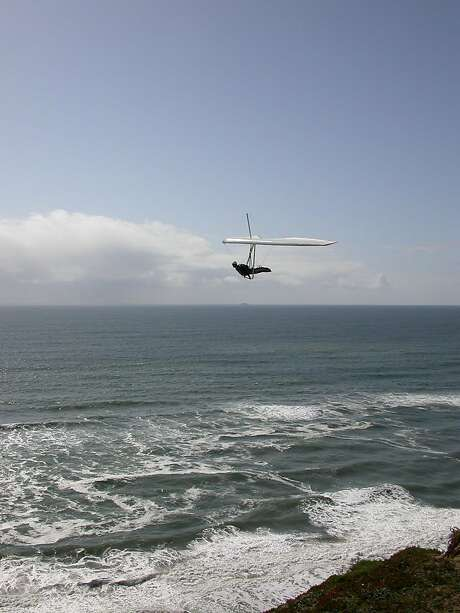 Hang glider sailing along San Francisco waterfront at Fort Funston south of Ocean Beach along Great Highway, photographed from popular cliff-top viewing area. Photo: Tom Stienstra/The Chronicle