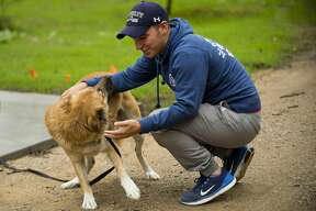 Christopher Williams reunites in Sanford with Lucy, a dog he helped rescue during his tour in Iraq. Williams, a Senior Airman in the U.S. Air Force, arrived home Sunday, Sept. 30, 2018. (Katy Kildee/kkildee@mdn.net)