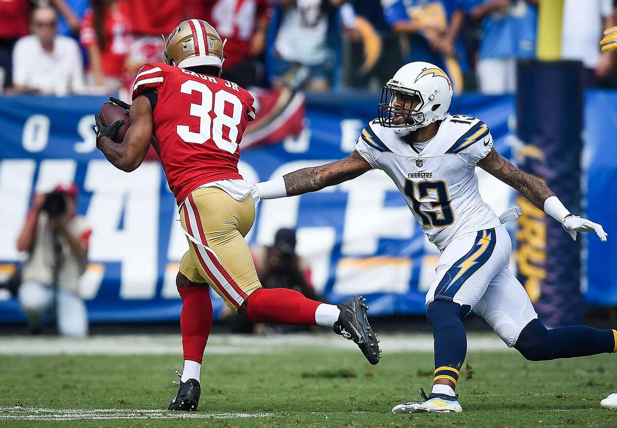 Defensive back Antone Exum #38 of the San Francisco 49ers dodges wide receiver Keenan Allen #13 of the Los Angeles Chargers to score a touchdown in the first quarter at StubHub Center on September 30, 2018 in Carson, California.