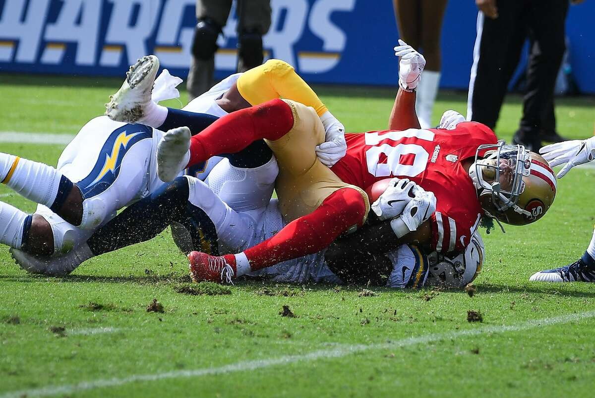 CARSON, CA - SEPTEMBER 30: Wide receiver Dante Pettis #18 of the San Francisco 49ers is taken down and injured on the play by outside linebacker Jatavis Brown #57 and defensive back Adrian Phillips #31 of the Los Angeles Chargers at StubHub Center on September 30, 2018 in Carson, California. (Photo by Jayne Kamin-Oncea/Getty Images)