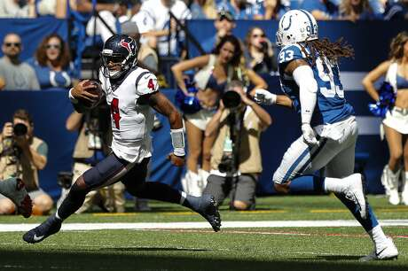 Houston Texans quarterback Deshaun Watson (4) runs past Indianapolis Colts defensive end Jabaal Sheard (93) for a first down during the first quarter of an NFL football game at Lucas Oil Stadium on Sunday, Sept. 30, 2018, in Indianapolis.