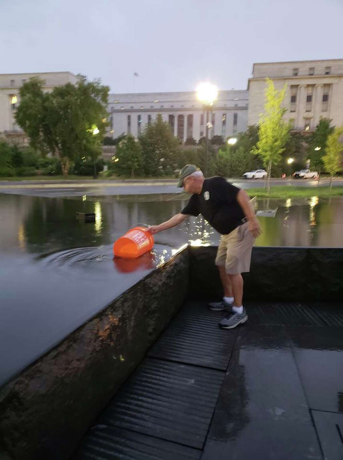 Melody Burns Joe Pollicino, president of the Tri-County Council of Vietnam Era Veterans fills a pail with water from the National Mall pool after he helps clean the the American Veterans Disabled for Life Memorial in Washington, D.C.