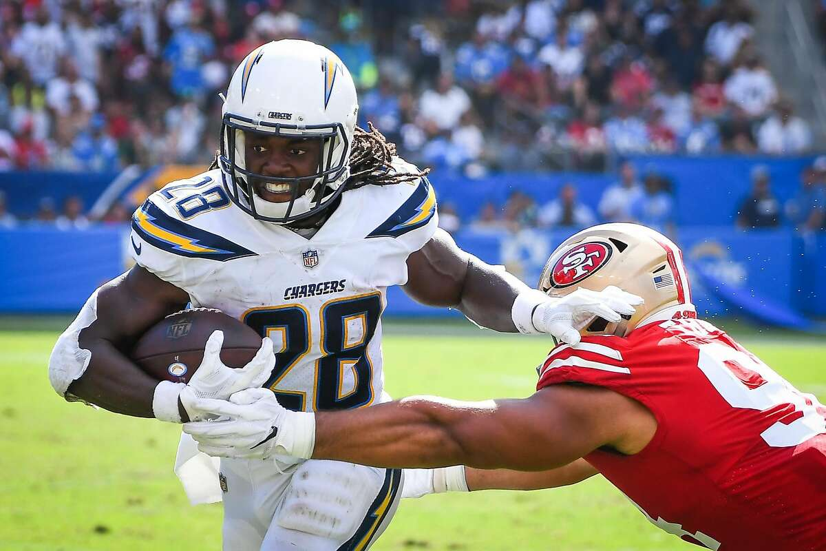 Running back Melvin Gordon #28 of the Los Angeles Chargers runs the ball by defensive end Solomon Thomas #94 of the San Francisco 49ers at StubHub Center on September 30, 2018 in Carson, California.