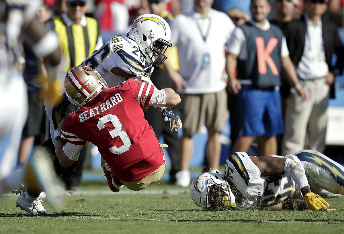 San Francisco 49ers quarterback C.J. Beathard, left, is hit by Los Angeles Chargers defensive back Casey Hayward, center, while running the ball as defensive back Derwin James lays on the ground during the second half of an NFL football game, Sunday, Sept. 30, 2018, in Carson, Calif.