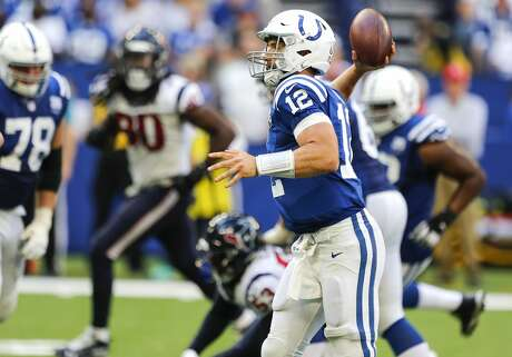 Indianapolis Colts quarterback Andrew Luck (12) rolls out to throw a 9-yard touchdown pass against the Houston Texans during the second half of an NFL football game at Lucas Oil Stadium on Sunday, Sept. 30, 2018, in Indianapolis. The Texans won 37-34.