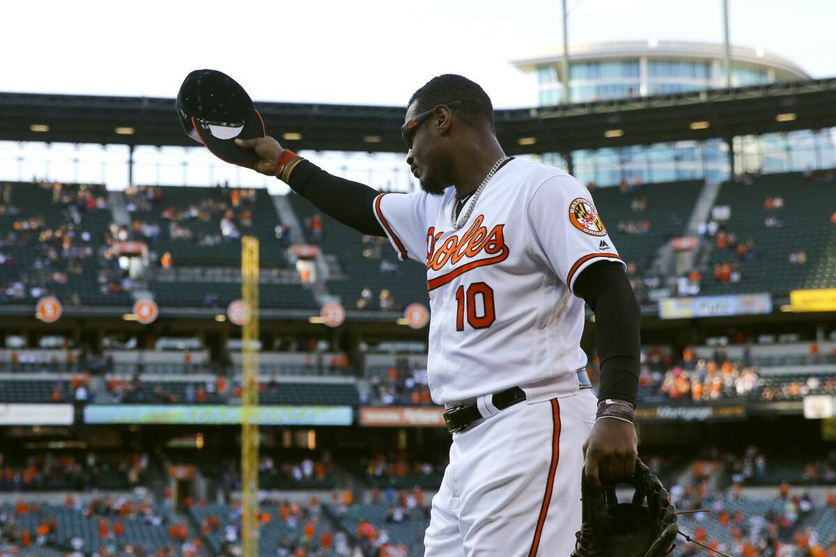 Baltimore Orioles' Adam Jones waves his cap to cheering fans as he is is pulled in the ninth inning of a baseball game against the Houston Astros, Sunday, Sept. 30, 2018, in Baltimore. Baltimore won 4-0. (AP Photo/Patrick Semansky)