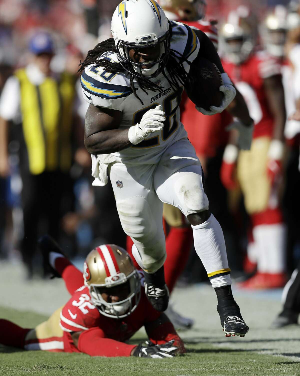 Los Angeles Chargers running back Melvin Gordon, top, escapes a tackle by San Francisco 49ers cornerback D.J. Reed during the second half of an NFL football game, Sunday, Sept. 30, 2018, in Carson, Calif. (AP Photo/Marcio Sanchez)