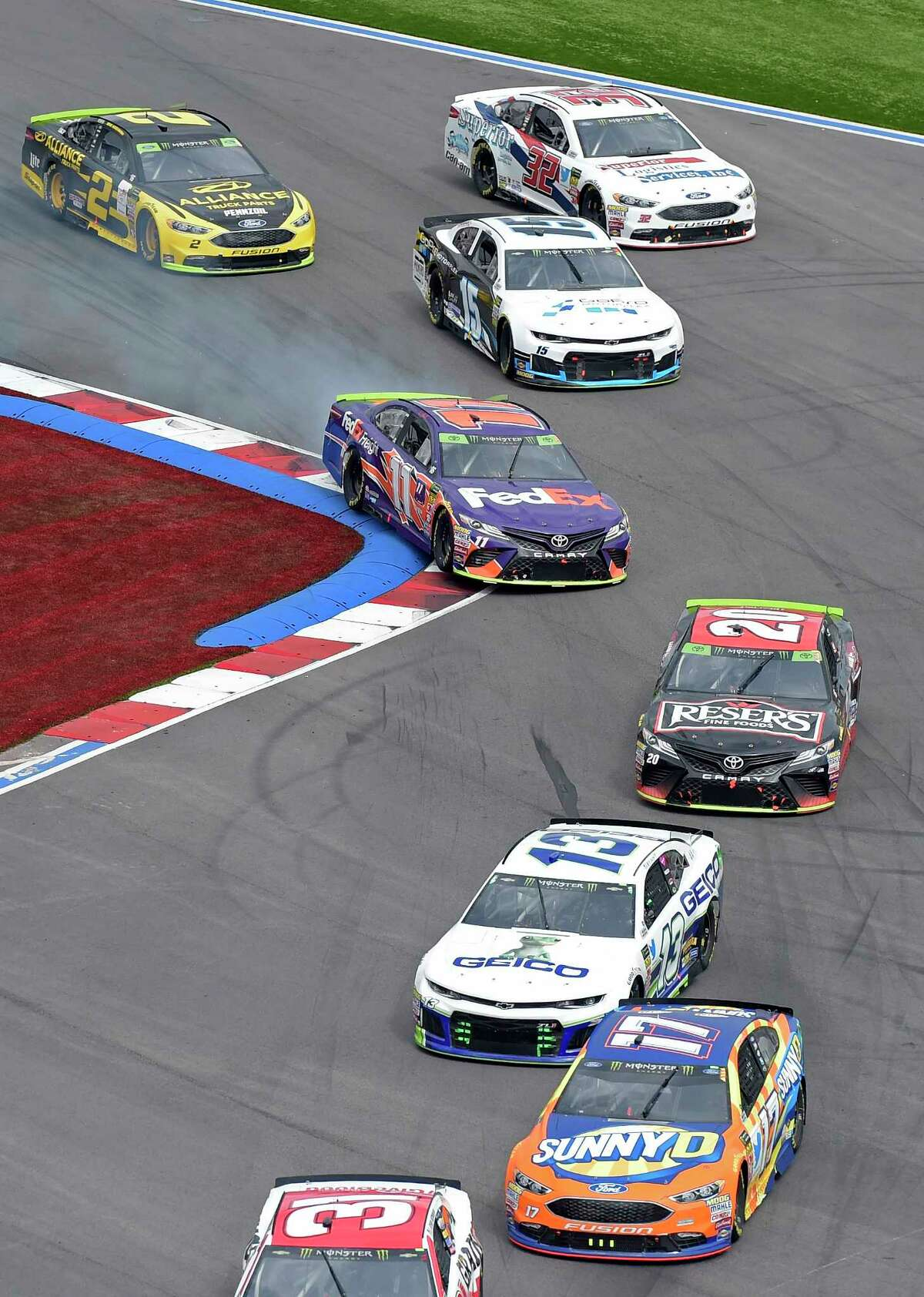 Denny Hamlin (11) runs over the rumble strips in Turn 16 during the NASCAR Cup series auto race at Charlotte Motor Speedway in Concord, N.C., Sunday, Sept. 30, 2018. (AP Photo/Mike McCarn)