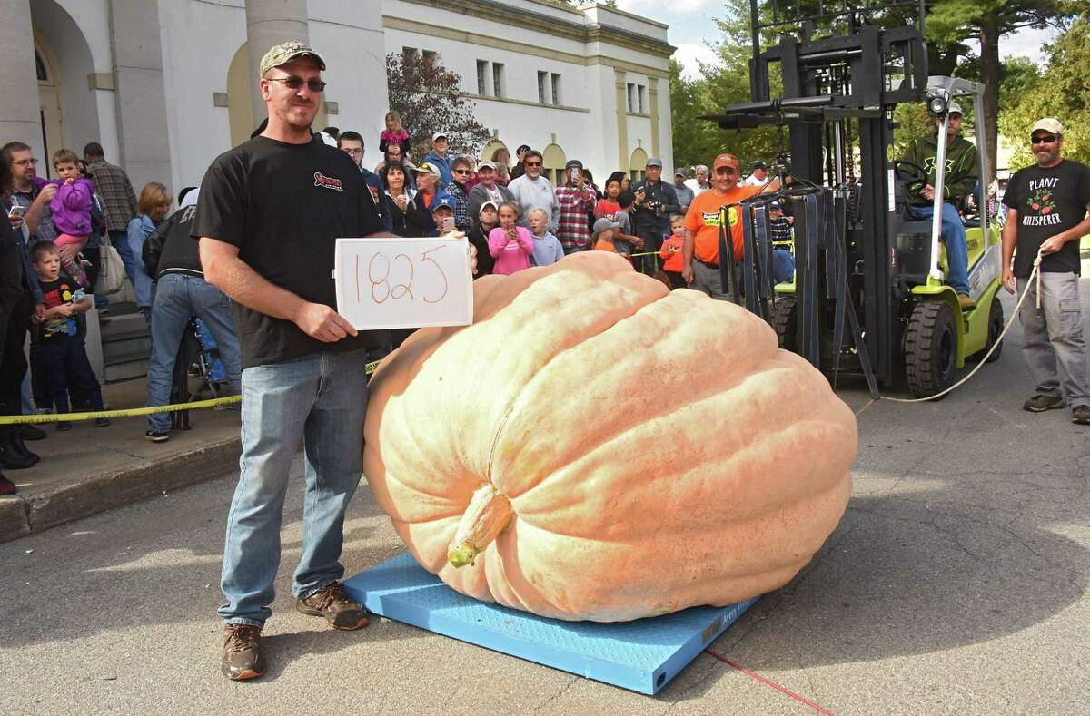 Chad Tucker of Brushton, N.Y. is seen with his 1,825 pound pumpkin as he is announced the winner during New York's Giant Pumpkin Weigh-Off held at the Lincoln Bathhouse at Saratoga Spa State Park on Sunday, Sept. 30, 2018 in Saratoga Springs, N.Y. The pumpkin started to grow on July 6 of this year. (Lori Van Buren/Times Union)