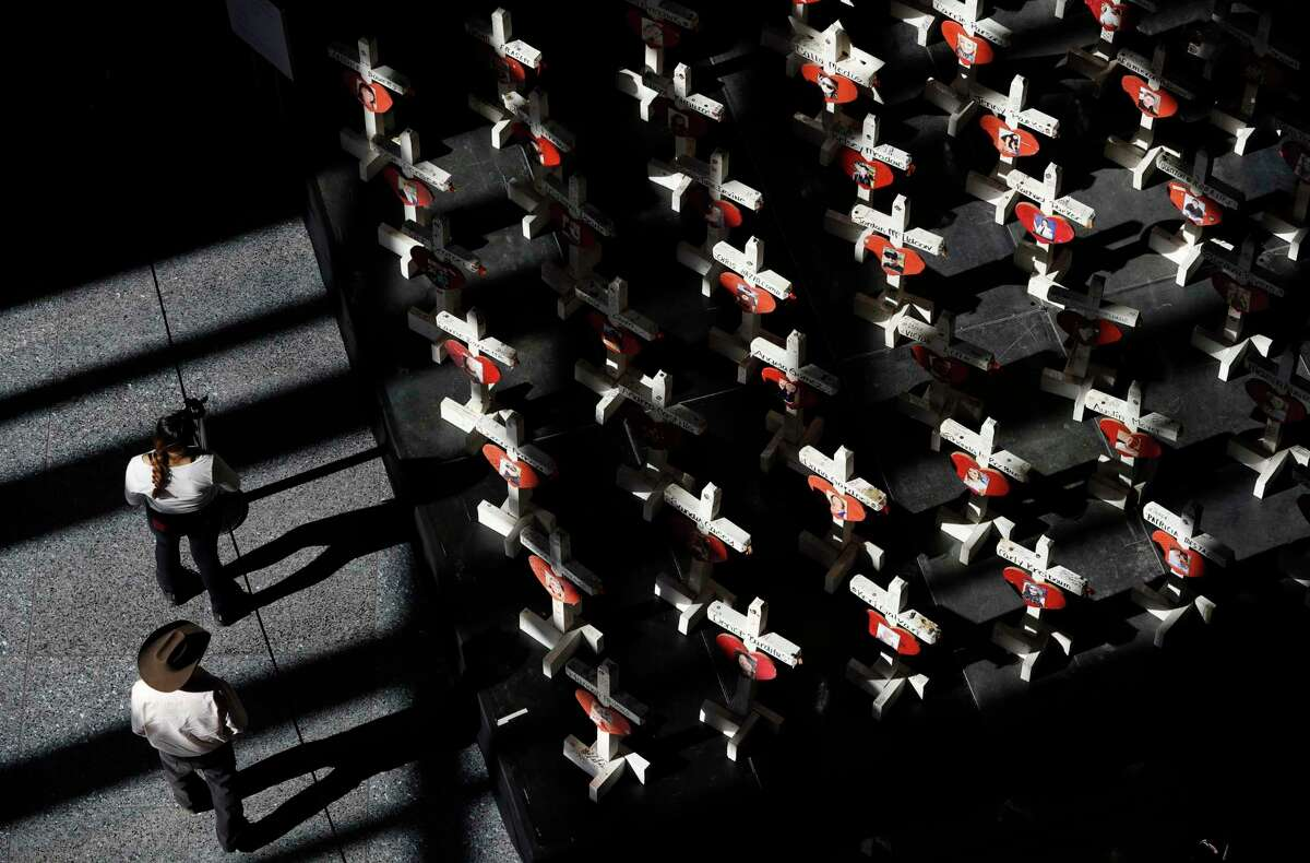 In this Sept. 25, 2018, photo, people look at a display of wooden crosses and a Star of David on display at the Clark County Government Center in Las Vegas. The crosses and Star of David had been part of a makeshift memorial along the Las Vegas Strip erected in memory of the victims of the Oct. 1, 2017, mass shooting in Las Vegas. (AP Photo/John Locher)