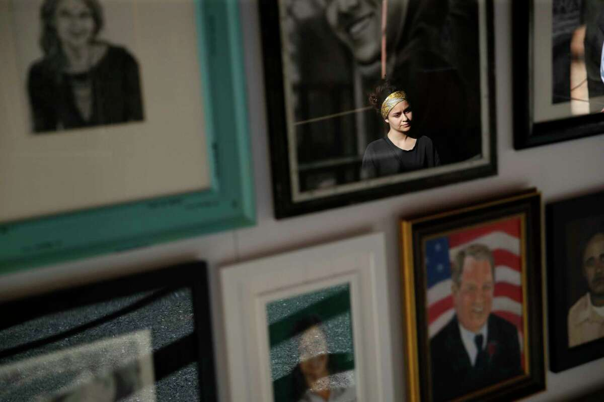 In this Sept. 25, 2018, photo, a woman looks at painted portraits of victims of the Oct. 1, 2017, mass shooting in Las Vegas on display at the Clark County Government Center in Las Vegas. (AP Photo/John Locher)
