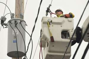 A National Grid employee works on power lines as firefighters work to extinguish a multi-home fire on Quail St. on Sunday, Sept. 30, 2018 in Albany, N.Y. The fire started about 4:40 AM. (Lori Van Buren/Times Union)